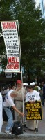 """Sign 1: """"Warning: atheist, drunk, liar, thief, sexual pervert, religious hypocrite: Hell Forever."""" Sign 2: """"Jesus must be your Lord or he will not be your Savior."""""""