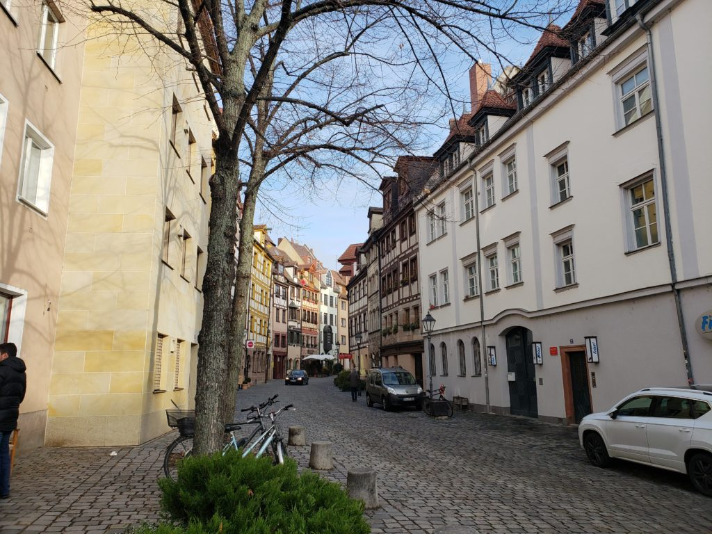 A narrow street in Nuremberg that's lined with three story buildings.