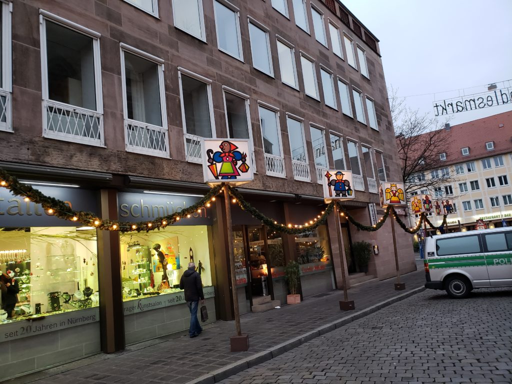 A row of storefronts in Nuremberg, with focus on the cartoonish decorations above the doors.