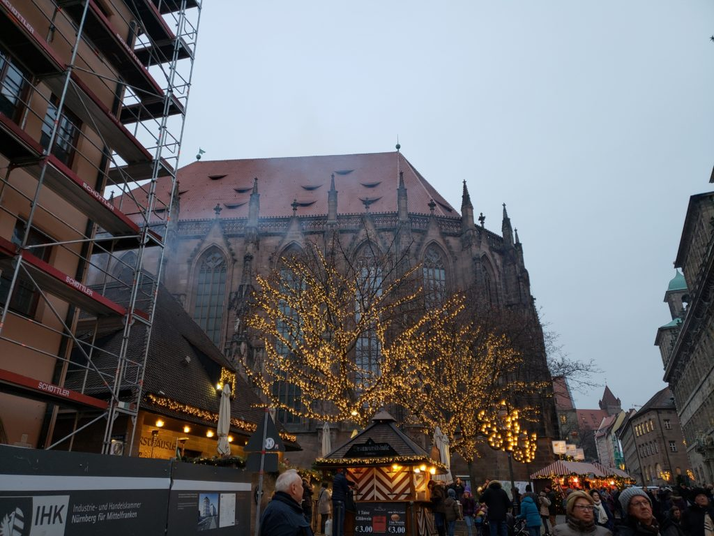 Lit trees and market stalls with a large building (likely a church) in the background.