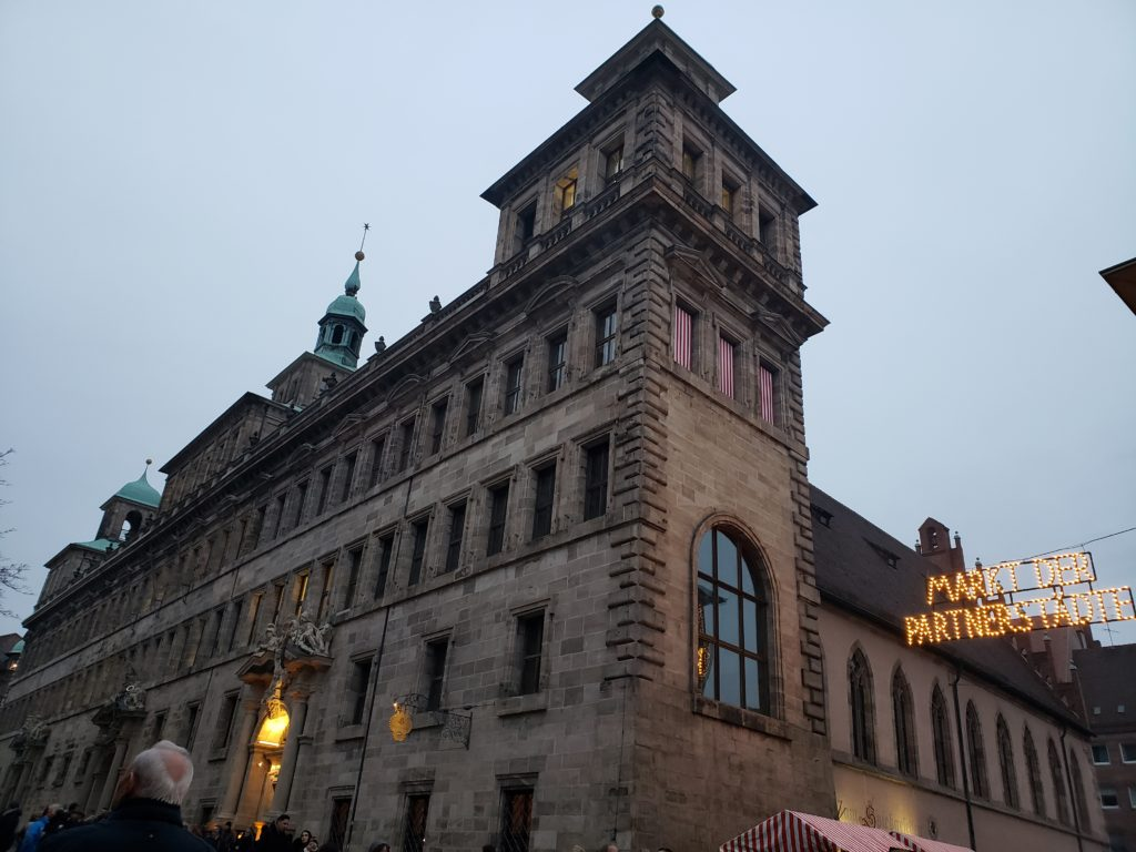 "A large, old building with a string of lights reading ""Market der Partnerstadte""."